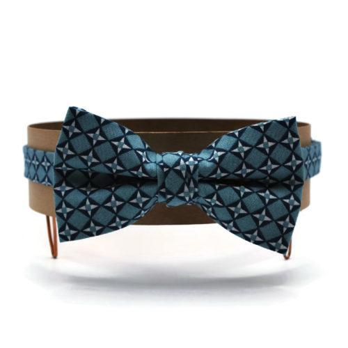 Voici le noeud papillon La Gloire de mon père en coton imprimé bleu clair au motif géométrique de losanges et de croix bleu marine et blanc.