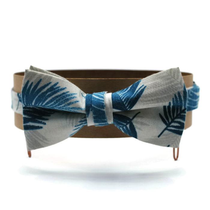 Voici un noeud papillon en coton blanc à motifs de feuille de palmes bleu turquoise et beige.