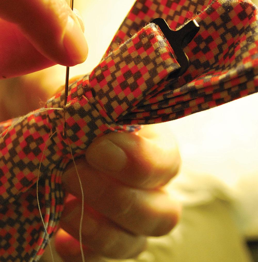 Plan serré sur une main en train de coudre un noeud papillon.